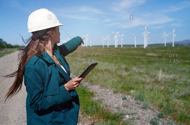 Environmental specialist with tablet computer at the wind turbines site