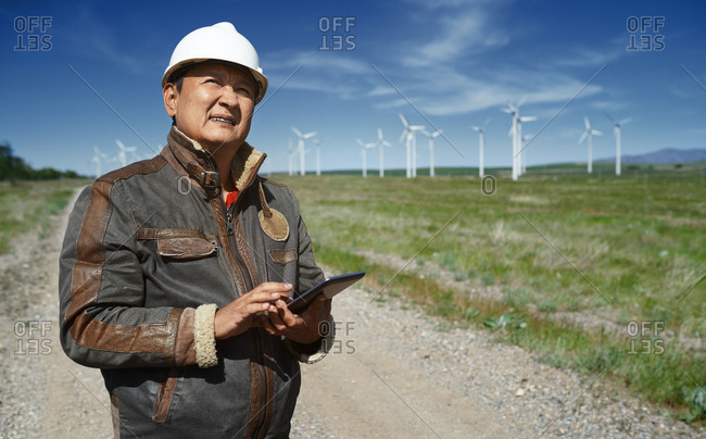 Environmental engineer with digital tablet at the wind turbines site