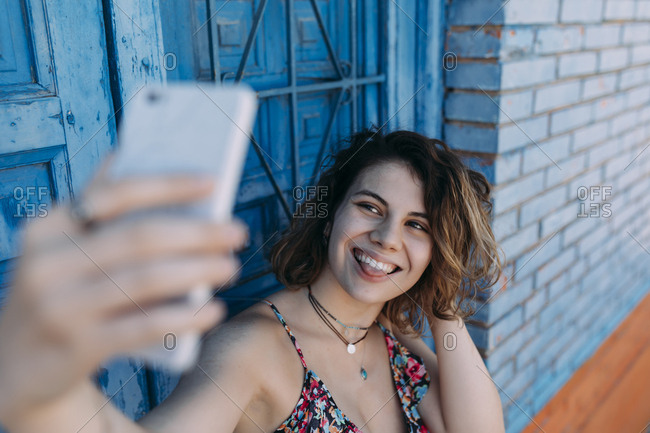 Young woman with silly facial expression taking a selfie with her phone