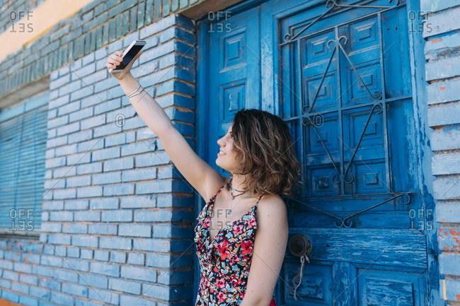 Smiling young woman taking a selfie with her phone