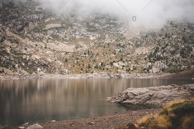 Foggy mountain reflecting in lake