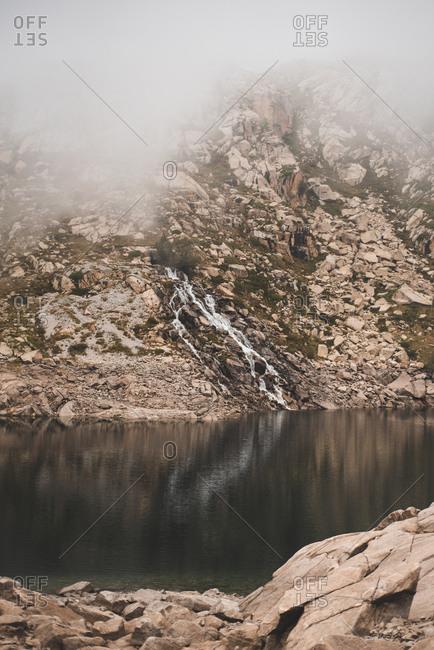 Foggy rocky mountain reflecting in lake