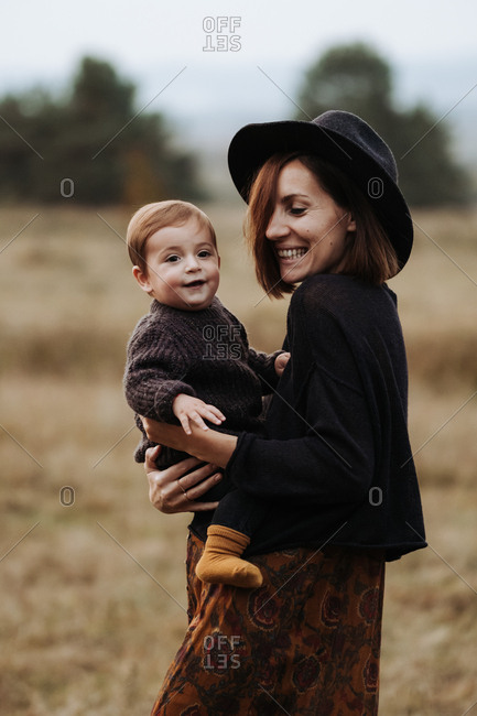 Smiling mother wearing a hat and holding her child