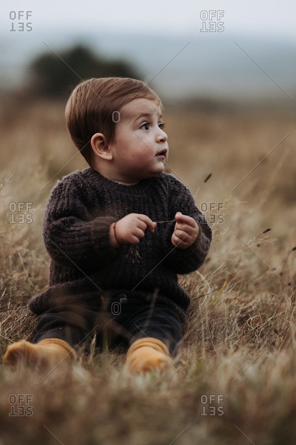 Toddler boy wearing brown sweater sitting in a field of dry grass and looking to side