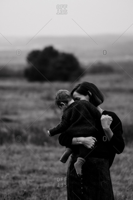 Mother holding her child while standing in a meadow