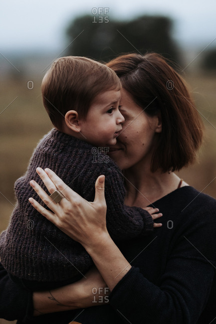 Portrait of a toddler child held by his mother