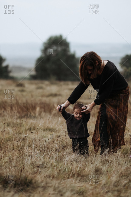 Mother helping her toddler child to walk in a field of tall grass