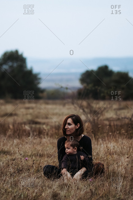 Mother and child sitting together in a field of tall dry grass