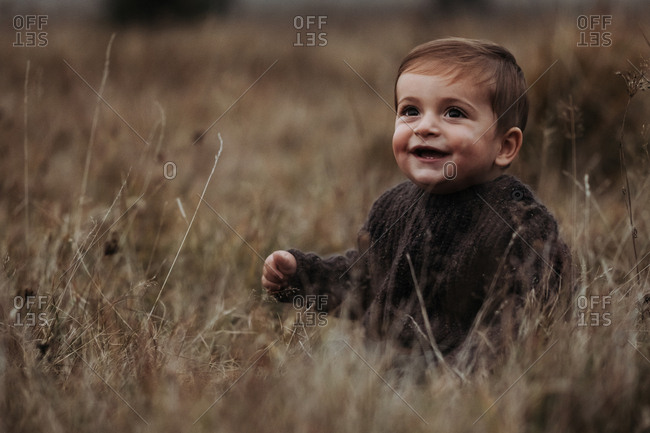 Portrait of a smiling toddler boy sitting in a field of tall grass