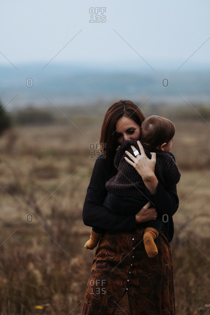 Mother holding her child close while standing in a field of golden grass