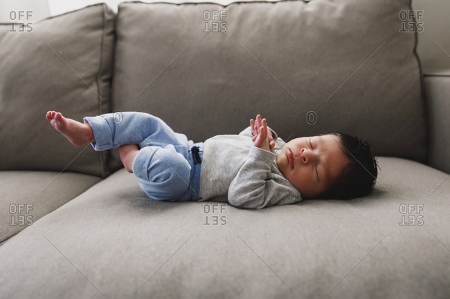 Newborn baby boy lying on couch
