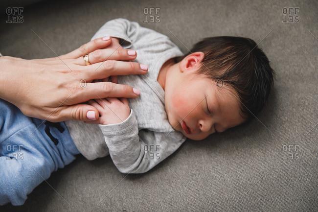 Mother's hand on sleeping newborn baby boy