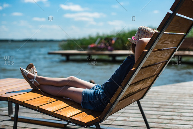 Girl relaxing on a lounger at a lake