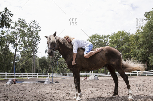 Senior Woman Lying On Horse And Hugging Him At Ranch
