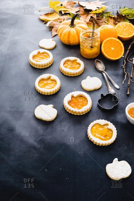 Studio shot of Halloween pumpkin cookies with orange jam