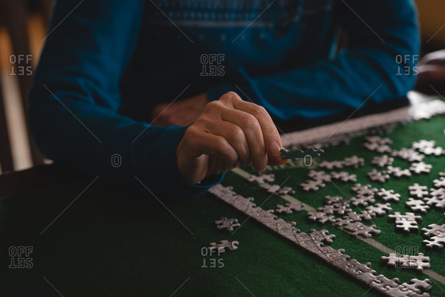 Mid section of senior woman playing jigsaw puzzle at home