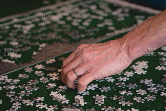 Close-up of senior man playing puzzle game at home