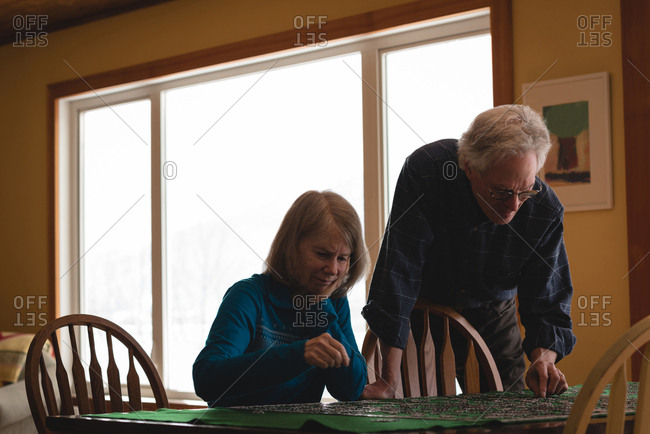 Senior couple playing jigsaw puzzle at home