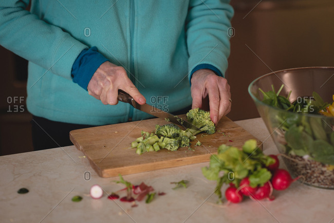 Woman chopping broccoli with knife on chopping board in kitchen