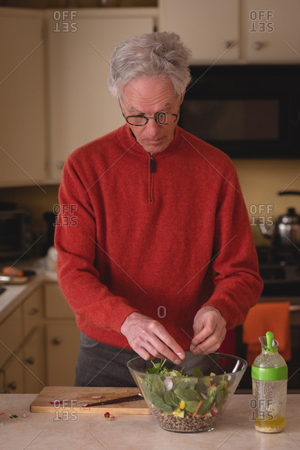 Senior man preparing salad in kitchen at home