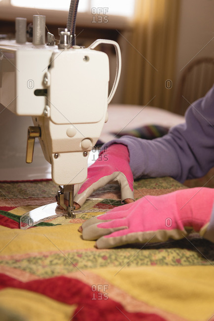 Woman sews clothes on sewing machine at home