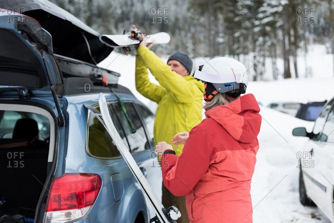 Senior couple keeping ski board on car roof during winter