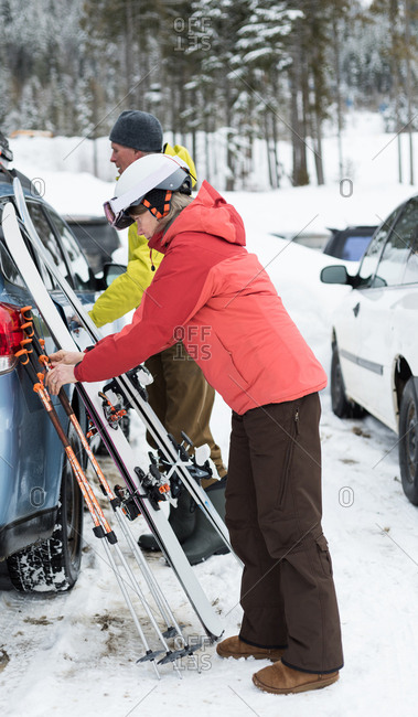 Senior couple keeping ski board and ski pole near car during winter