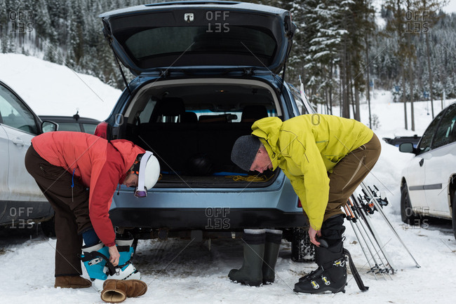 Senior couple wearing ski boot near car
