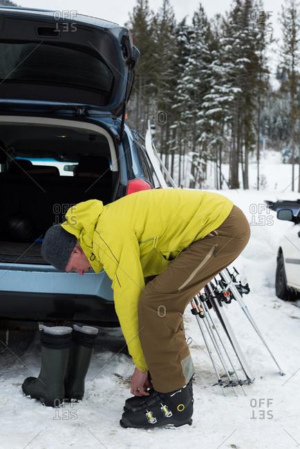 Senior man wearing ski boot near car