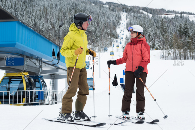 Senior couple in ski attire ready to ski in snowy region