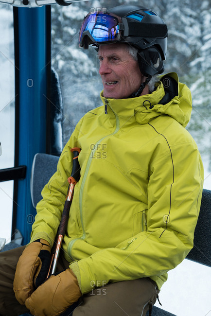 Smiling senior man travelling in ski lift