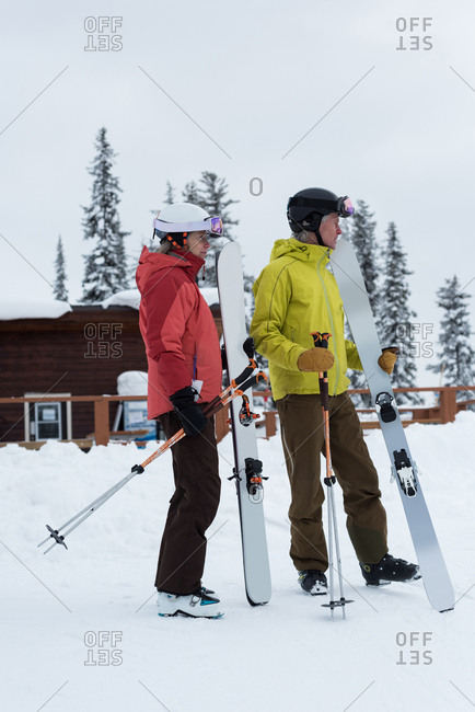 Side view of senior couple standing with ski board and ski pole on snowy landscape