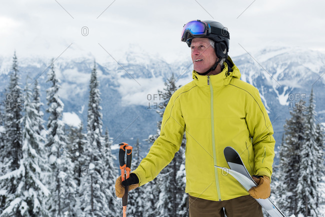 Smiling senior man with ski pole and ski board standing in snowy region
