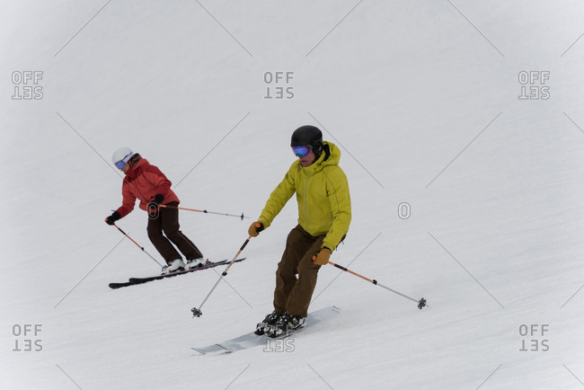 Skier couple skiing on snowy landscape during winter