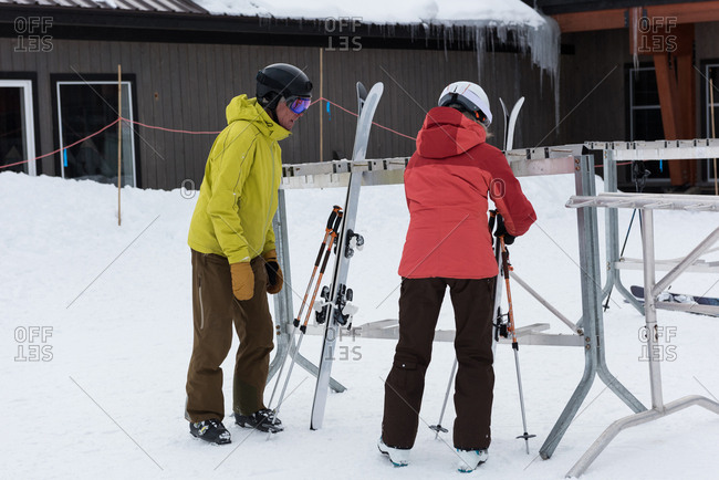 Senior couple arranging ski board on rack in snowy landscape