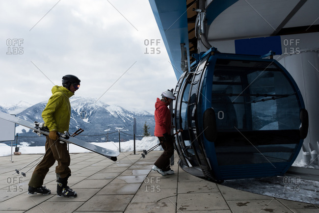 Couple with ski board entering into ski lift during winter