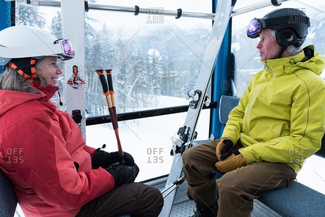 Smiling couple travelling into ski lift