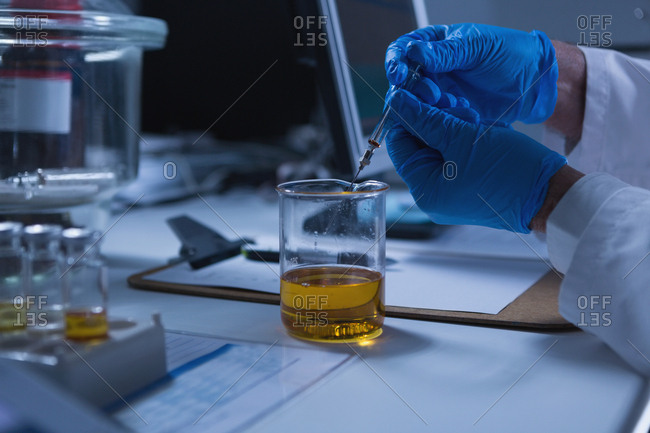 Close-up of male scientist experimenting in laboratory
