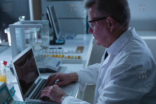 Side view of male scientist using laptop in laboratory