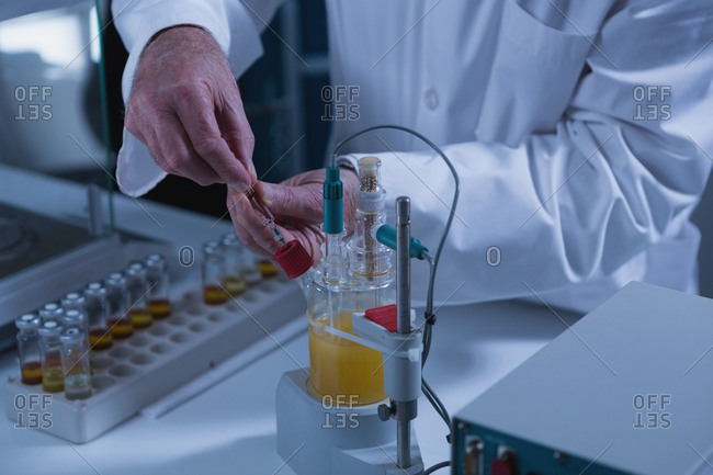 Mid section of male scientist experimenting in laboratory