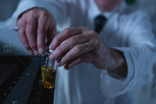 Male scientist placing medical vials on a lab machine in laboratory
