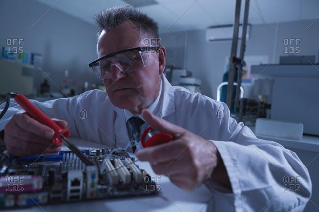 Male scientist soldering circuit board in laboratory