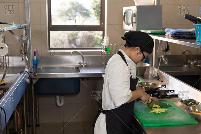 Female chef cutting vegetables in kitchen at restaurant
