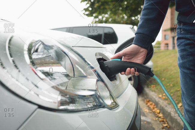 Close-up of man charging electric car at charging station