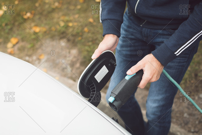 Mid section of man charging electric car at charging station