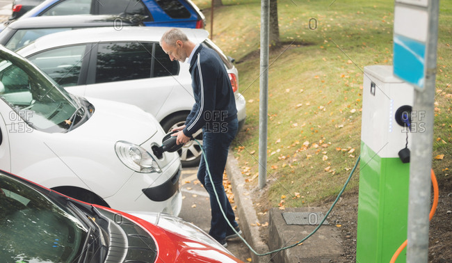Side view of man charging electric car at charging station