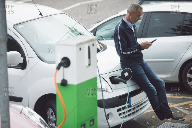 Man using mobile phone while charging electric car at charging station