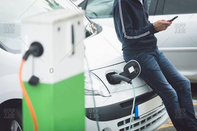 Mid section of man using mobile phone while charging electric car at charging station
