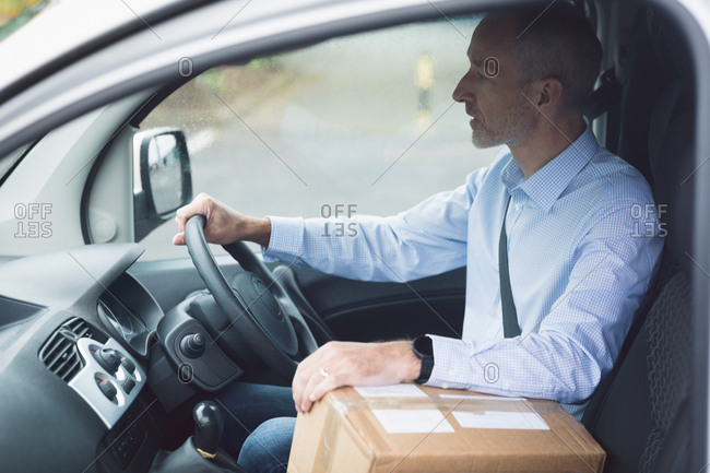 Side view of delivery man with package driving a delivery van