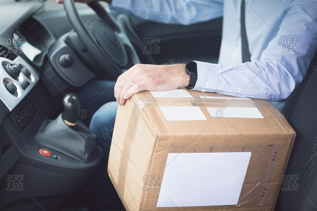 Close-up of delivery man with package driving a delivery van